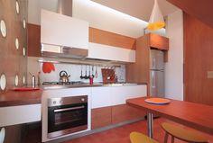 Na pequena cozinha, o destaque é a marcenaria com desenho da arquiteta Monica Drucker e execução da Roma Móveis. As peças foram estruturadas em MDF e têm acabamento em madeira tauari e laminado melamínico branco, onde forno, fogão, coifa e geladeira ficam embutidos. A casa Madrid está em um condomínio residencial de Marília, interior de São Paulo