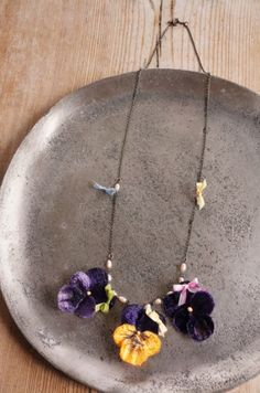 I love pansies. This necklace certainly looks like these are pansies on it.