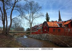 Vasteras, Sweden - 8 April, 2018: Trees in early spring on shore of Black river with swedish style houses and Vasteras Cathedral, Idyllic nordic cityscape