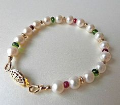 This handmade bracelet is a simple strand of high quality 7mm round white pearls strung together with genuine opaque red rubies, AAA emerald green faceted Russian chrome diopside gemstones, and 14K gold filled beads. The bracelet is 7 1/4 inches long and closes with a 14K gold