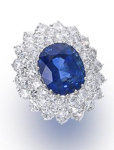 A sapphire and diamond ring centering an oval-shaped sapphire, weighing 12.10 carats, within a three tiered round brilliant-cut diamond surround; estimated total diamond weight: 5.20 carats; mounted in platinum