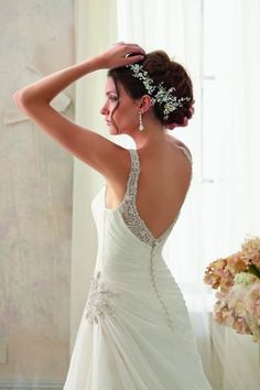 This lavish Mori Lee Blu 5213 wedding dress is a true work of art. Soft pleats gently wrap the bodice and are gathered at the hip with a stunning starburst detail made of clear crystals and faux pearls. More faux pearls and crystals adorn the sweetheart neckline, straps, and backline in a meticulously hand-placed pattern. Plunging into a V, the back fastens with a long row of bridal buttons while the A-line skirt falls in sweeping diagonals and finishes in a chapel length train.