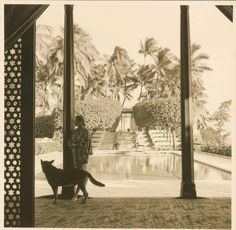 Photograph of Doris Duke and one of her dogs, standing in the Playhouse with the pool in the background. 1960-1965.  (Courtesy Shangri La, Doris Duke Foundation for Islamic Art. Doris Duke Charitable Foundation Historical Archives, David M. Rubenstein Rare Book & Manuscript Library, Duke University, Durham, North Carolina)