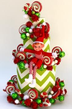 Our three tiered FLORAL & CRAFT BASE wrapped in green/white chevron fabric displaying holiday garland and the ELF on a SHELF.  A festive highligh to your holiday table!