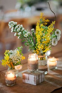 A beautiful way of using different sizes of jar for candles and flowers.