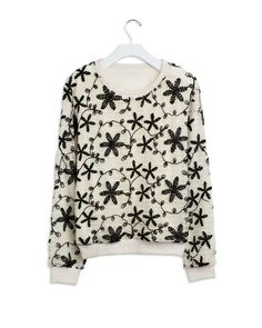 Embroidered floral pullover with knitted overlay. This fun sweater has a subtle shimmer from small sequins knitted throughout.