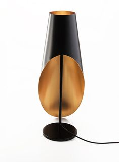 A sophisticated lamp by Andrey Dokuchaev that was inspired by the silhouette of a tuxedo or the long train of an evening gown made in black and gold.