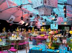 The dining room treats the 700 guests to a fanciful world based on Alice motifs, including a stage backdrop with three-dimensional chess pieces, checkerboard dance floor, and chandeliers created from oversize playing cards.