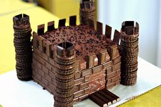 Chocolate cake covered with chocolate bars, stacks of chocolate sandwich cookies at corners make a cute castle cake.