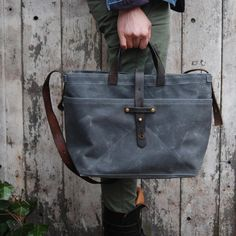 Waxed Canvas Totes, by Peg and Awl, feature well-worn, comfortable handles that are recycled from Swedish WW2 gun holsters. Peg and Awl fashion items by hand from scavenged materials: wood, leather, slate.