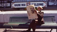 A man reading The Press, with news of Dick Tayler's gold on the front page, in Cathedral Square outside the Regent Theatre in Public Square, Meeting Place, Conversation, Theatre, Cathedral, Reading, News, Gold, Theater