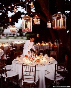 Dangling Rose Lanterns    For a midsummer night's meal at an outdoor reception, string lanterns hanging on chains from strong low-hanging branches. Small and large, these lamps hold ivory tapers, their bases disappearing in a thick layer of fresh, fragrant rose petals.