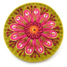 Flower brooch made of scrap fabric pieces embroidered onto a felt circle base.  Gorgeous work;