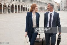 Stock Photo : Smiling businessman and businesswoman pulling suitcases through St. Markês Square in Venice