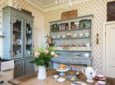 Painted dressers and wallpaper in kitchen