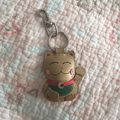 """Maneki-neko key charm This is a gold leather hand-made Maneki-neko """"beckoning cat"""". It's a common Japanese figurine which is often believed to bring good luck to the owner.   Pre-owned and loved ❤️ got as a gift . Hardware is a bit tarnished. Can be used with your keychain, wallet, bag; basically anywhere you want to carry him. Very cute, needs a new home. Accessories"""