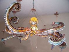 """""""This awesome stained glass octopus chandelier was made by Mason Parker of Mason's Creations. Each of the tentacles is detachable, and the entire octopus is four feet across. You can adjust the lighting by illuminating just the center, just the tentacles, or all of it together."""" #Home #Chandelier #Awesome My Glass, Toilet Room, Octopus, Bathroom Toilets, The Creator, Stained Glass, Light Fixtures, Steampunk, Sea Creatures"""