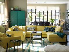 Grand canapé jaune en U installé au centre d'un séjour/salle à manger décloisonné.
