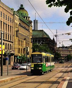Tram on the Mannerheim Road in Helsinki, Finland. The dark grey facade of the wonderful and iconic Stockmann department store is visible in the rear ground
