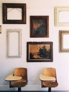 Gallery wall of antique frames and paintings over vintage wood school desks - Art Walls