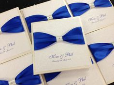Royal blue ribbon on white floral embossed card layered on Oyster in a traditional fold style invitation with a pocket inside