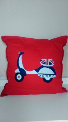 A striking red fabric cushion with felt applique detail of a union jack design scooter. The cushion measures appoximately 38 x 38cm square. Each cushion is provided with a cushion pad.  This item is custom made to order so please allow 2 weeks for making and then upto a week for delivery. Orders will be posted using myHermes and a tracking number will be supplied once dispatched.