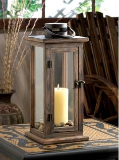Lodge Wooden Lantern | Wood, metal and glass combine to create the ideal candle lantern, with a design that is equally familiar and fantastic. This inspired lighting accent features a stained wood framework, a fascinating top loop for hanging, and a vintage-inspired metal door latch. The elongated glass panels let the light from your candle shine bright.
