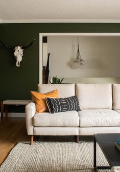 A beautiful mid-century living room featuring forest green walls, plants and a leather couch. #midcenturylivingroom #greenlivingroom #greenpaint #forestgreenpaint