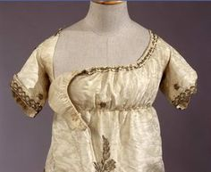 Early 19thC. Italian. Gala dress in white moire silk, embroidered in silver gilt thread, with bib-front closure.