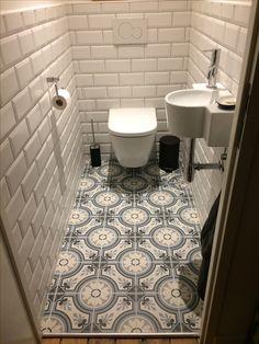 Carrelage imitation carreaux de ciment Revoir Paris et carrelage métro dans petite toilette avec wc suspendu et petit évier. Photo @l_amande