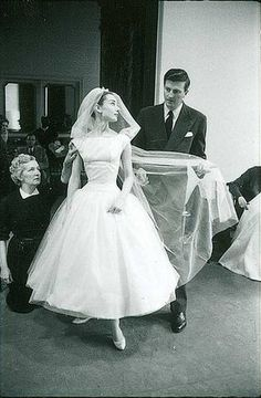 Audrey Hepburn being fitted for her 'Funny Face' wedding dress by Hubert de Givenchy.