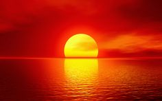 Bright yellow sunset over bright red sky reflected on the water