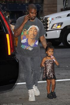Daddy's girl: The Waves rapper kept watch over North while taking a quick phone call