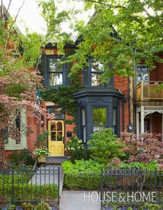 Toronto interior designer Jeffery Douglas offset this home's deep black trim with a golden yellow door — a traditional Victorian accent that lifts and brightens the black. The lush garden and wrought-iron fence supply even more charm. | Photographer: Michael Graydon