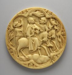 14th cent Mirror-case; France. ivory; carved; circular; depicts knight and lady on horse-back; both carry hawks; on left is figure blowing horn; scene enclosed in seven foil border with masks; thinned with lathe. Lady is wearing a hood.