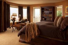 Dormitorio cálido en marrón. Cortinas en el ventanal