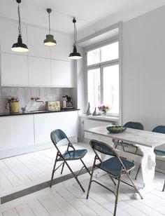 Två industrilampor och en grön bumlinglampa lyser upp i köket. Skåp, diskho och vitvaror från Ikea. Olika sorters kakelplattor ger struktur. (Sköna Hem)