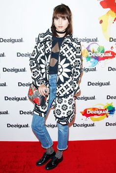 Langley Fox wearing a printed coat, blue top with sheer detail, cropped high-waisted jeans, striped socks, and black leather oxfords at the Desigual F/W 15 show