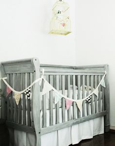Previously black crib painted grey and whitewashed.  Would definitely have to research safe paint...and the bunting on the side would have to go...definite strangulation hazard