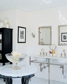 The master bath evokes a black-and-white color scheme. The center of the room is dominated by an ornate marble-topped table whose mate is in the living room.