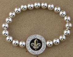 Bracelet Fleur De Lis Crystal Accents Our silver charms are made of lead free pewter. They are sterling plated then lightly antiqued and this plating process causes them to show extraordinary details.