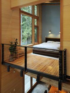 Loft com guarda corpo metálico e estrutura em madeira.