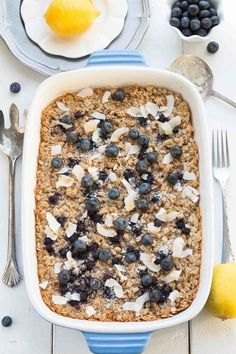 Delicious Blueberry Lemon Coconut Baked Oatmeal in a white and blue casserole dish with two silver forks next to it.