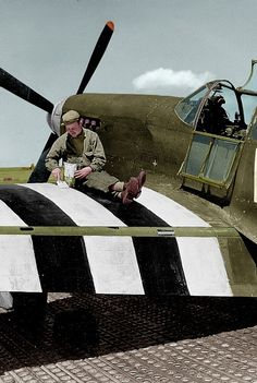 Painting D-Day invasion stripes on a P-51 Mustang (1944, colorized)