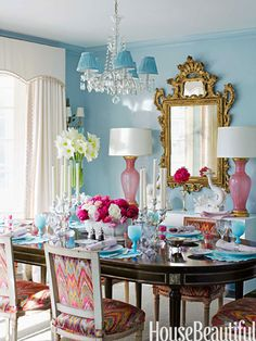 In the dining room, walls in Farrow & Ball's Blue Ground in Full Gloss are a foil for pink Murano glass lamps from Swank Lighting. Chairs are covered in Talcy Velvet by Clarence House.