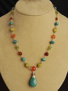 Far Vista Necklace, $120 / Harmony Scott  Faceted orange and red carnelian, turquoise, peridot, and yellow jade accented with delicate links, all come to point with an incredible center piece of Turquoise with a fine wire wrap and multi-gem cluster.