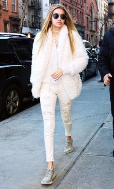 Gigi Hadid wears a lace-up sweater, shearling coat, distressed boyfriend jeans, Yeezy Boost sneakers, and round sunglasses