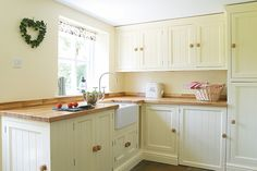 Cream kitchen with butchers block work top. Accessories with pastel blues