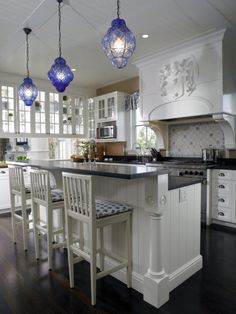 A beautiful white kitchen wirh accents of blue   love the pendants