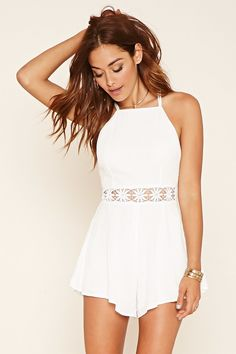 A woven gauze romper with cami straps that crisscross at the back, a concealed side zipper, and floral crochet detailing along the waist.